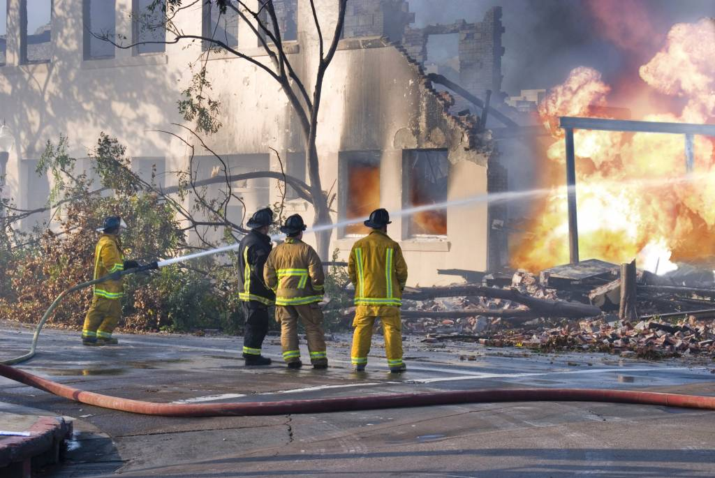 Four fire men taking control of a building fire